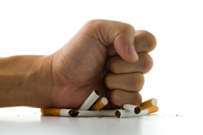 man s hand crushing cigarettes